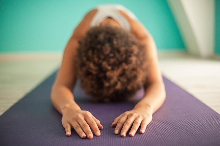 Mujer haciendo postura de yoga gurpranam